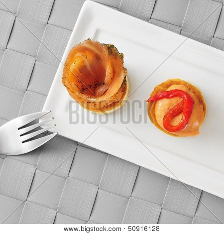 a plate with some different volauvents, one filled with smoked salmon and the other one filled with red pepper and cheese sauce, served as appetizer