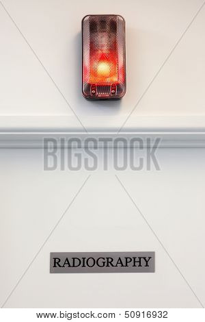 Radiography door with illuminated red light above.