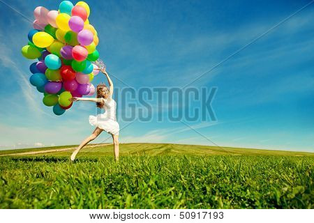 Happy birthday lady against the sky with rainbow-shaded air inflatables in hands. sunny and positive