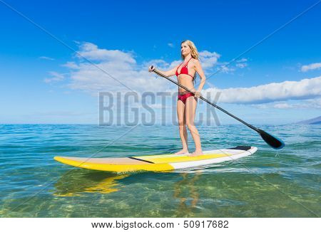 Young Attractive Woman on Stand Up Paddle Board, SUP, in the Blue Waters off Hawaii, Active Life Concept