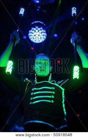 Performance of a man with a terrible pupils in samurai garb with glow sticks in stage with light ball