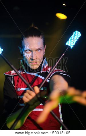 Performance of a man with tattoo and terrible pupils in samurai garb with glow sticks, sticks crossed in one hand.