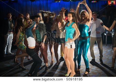 Fourteen young people having fun and dancing at a party