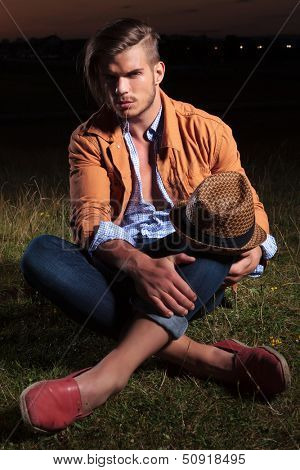 casual young man sitting outdoor and holding his hat on his knee while looking into the camera with a straw in his mouth