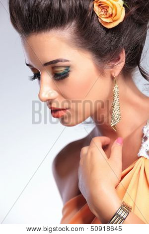 closeup photo of a young fashion woman looking away from the camera while touching her neck. on gray background