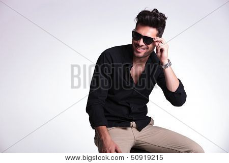 young fashion man sitting on a chair and adjusting his sunglasses while smiling and looking away from the camera. on a light background