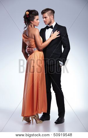 full length portrait of a young fashion couple with the man holding and looking at the woman while she holds her hand on his chest and looks away. on gray background