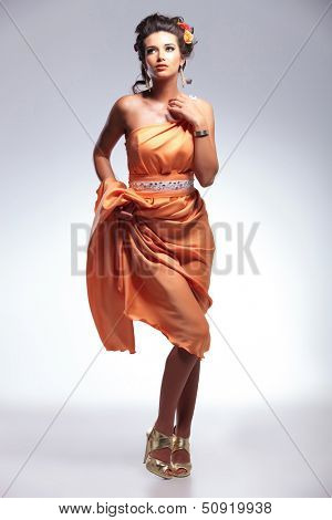 full length picture of a young fashion woman looking up,away from the camera while lifting her dress and revealing her legs. on gray background