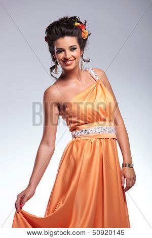 young fashion woman holding up her dress with her hand and smiling for the camera. on gray background