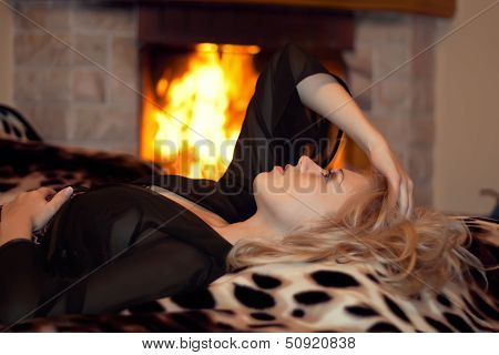 The Girl Is Heated At A Fireplace