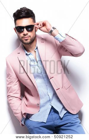 young casual man adjusting his sunglasses while holding a hand in his pocket and looking into the camera. on white background