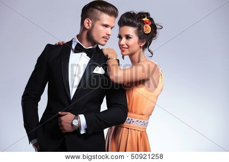 young fashion couple with woman behind man resting her hands on his shoulders while looking at him. on gray background
