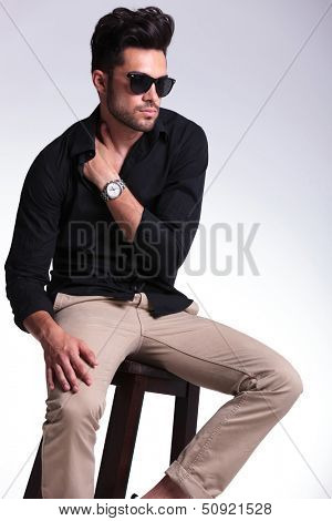 young fashion man sitting on a chair and looking away while holding his hand tucked in his shirt, at his shoulder. on a light background