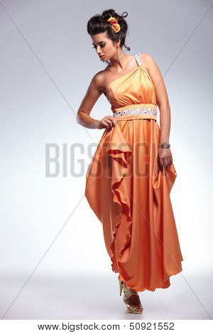 full length picture of a young fashion woman looking down and holding her dress with one hand. on gray background