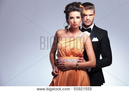 young fashion couple with man behind woman holding her with both hands while both looking at the camera. on gray background
