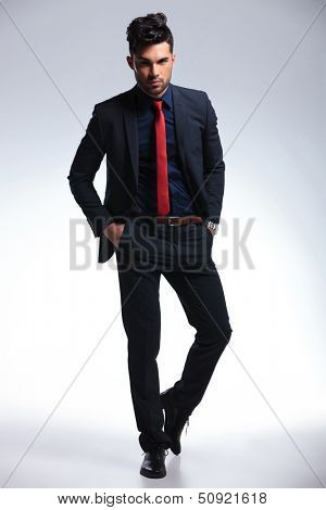 full length photo of an elegant young fashion man in tuxedo holding both hands in his pockets and looking at the camera. on gray background