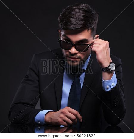young business man taking off his sunglasses and looking into the camera over them. on black background