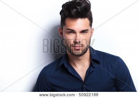 closeup portrait of a serious young fashion man looking straight into the camera. on a light background