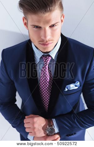 closeup of a young business man looking up at the camera while adjusting his cuffs. on a gray background