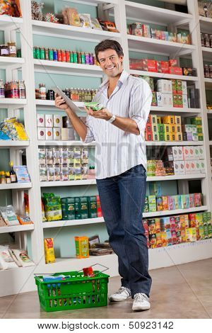 Full length portrait of happy mid adult man checking list on digital tablet in grocery store