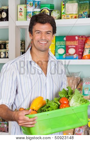 Portrait of happy mid adult man with vegetable basket in grocery store
