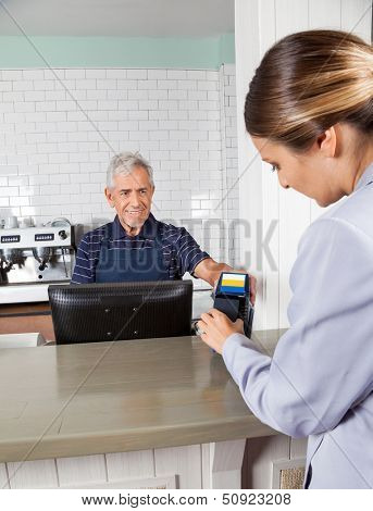 Mid adult woman making payment through mobilephone while senior cashier holding electronic reader at counter