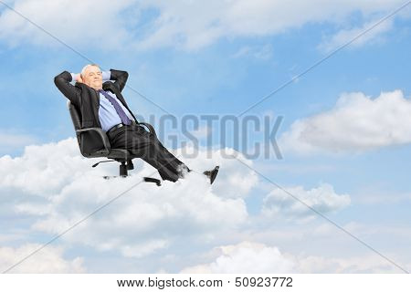 Mature businessman in suit resting in armchair and floating on a cloud