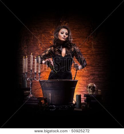 Beautiful witch making the witchcraft isolated on black. Halloween image.