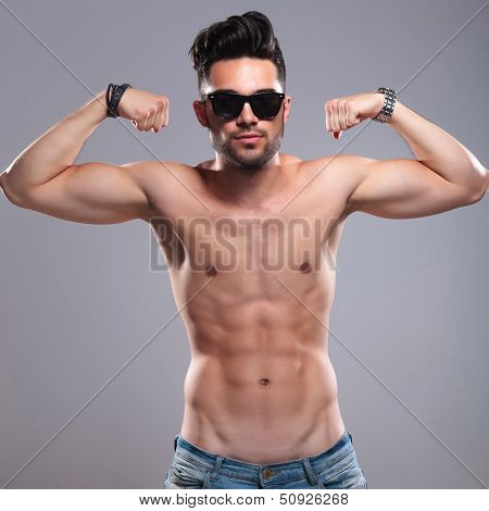 topless young man flexing his biceps while looking into the camera. on gray background