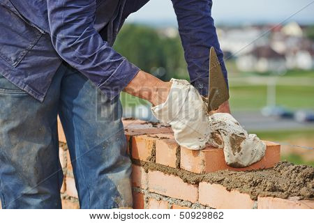 Close-up of construction process mason work with brick installation by trowel putty knife outdoors