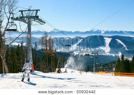 Snowborder going down the slope at ski resort