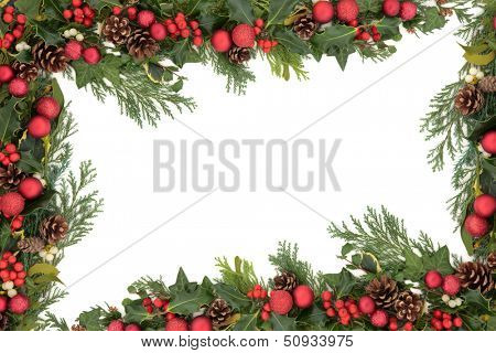Christmas background floral border with red baubles, natural holly, mistletoe, ivy, fir leaf sprigs and pine cones over white.