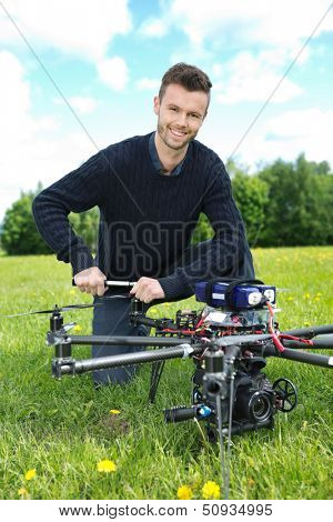 Portrait of young engineer fixing propeller of octocopter in park
