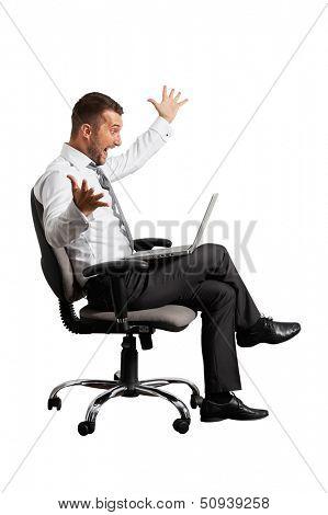 joyous businessman looking at laptop. isolated on white background