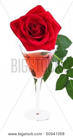 red rose and liquor in a celebratory glass