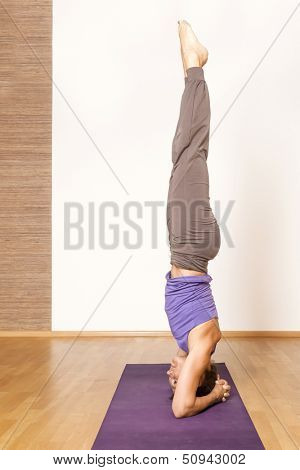An image of a pretty woman doing yoga - Salamba Shirshasana Head Stand