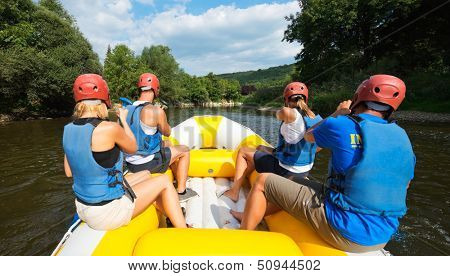 A group of friends in an inflatable raft moving down a river