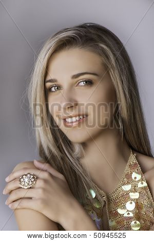 Portrait of beautiful blonde woman in gold with ring