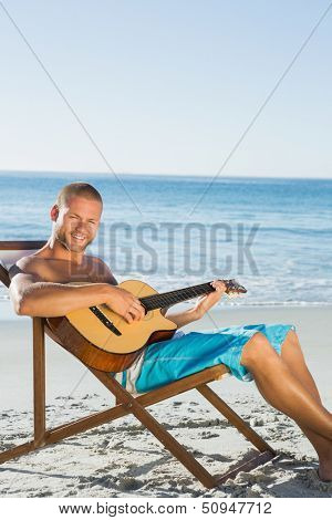 Cheerful handsome man strumming guitar on the beach