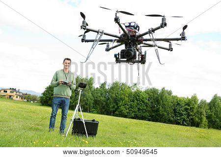 Happy young male technician flying UAV octocopter with remote control in park
