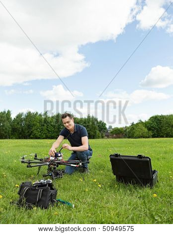 Young technician preparing multirotor helicopter in park