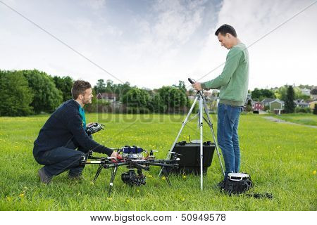 Side view of young engineers working on UAV helicopter in park