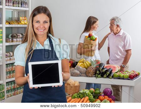Portrait of saleswoman displaying digital tablet with father and daughter communicating in background