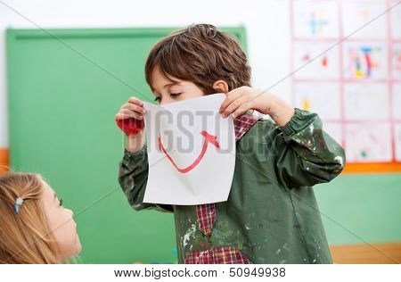 Playful little boy holding paper with smile drawn on it while looking at girl in art class