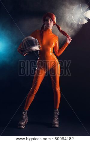 Sexy girl in orange latex catsuit holding helmet, sci-fi setting