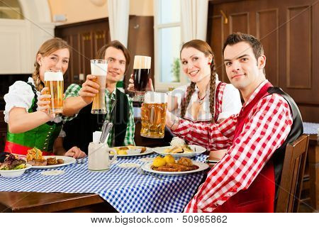Young people in traditional Bavarian Tracht eating in restaurant or pub lunch or dinner, they toast towards the camera