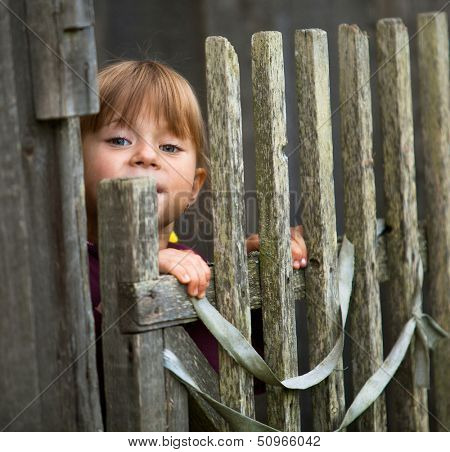Child standing near vintage rural fence.