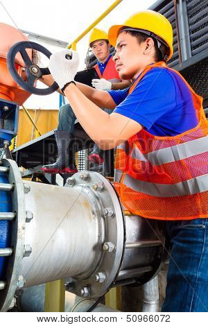 In utility or factory ewo technicians or engineers working on a valve on building technical equipment or industrial site