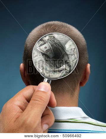 Looking to a mans head thinking about money through magnifying glass