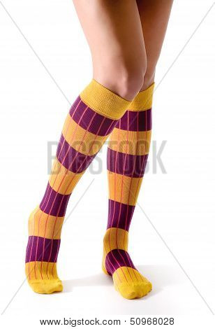Young Woman Legs Posing With Purple And Yellow Striped Socks